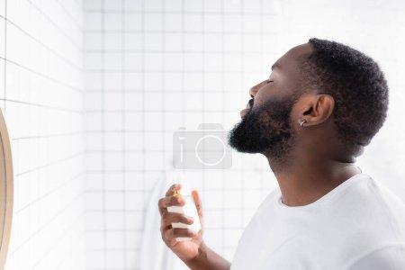 Photo pour Homme afro-américain en t-shirt blanc parfumé - image libre de droit