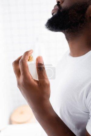 Photo pour Vue recadrée de l'homme afro-américain en t-shirt blanc à l'aide de parfum - image libre de droit