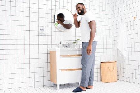 Photo pour Longueur totale de l'homme afro-américain brossant les dents et regardant en arrière - image libre de droit