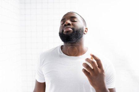 Photo pour Portrait d'homme afro-américain en t-shirt blanc parfumé - image libre de droit