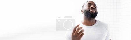Photo pour Prise de vue panoramique de l'homme afro-américain en t-shirt blanc au parfum - image libre de droit