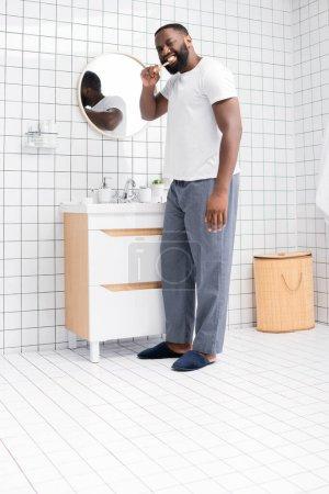 Photo pour Longueur totale de l'homme afro-américain brossant les dents dans la salle de bain - image libre de droit