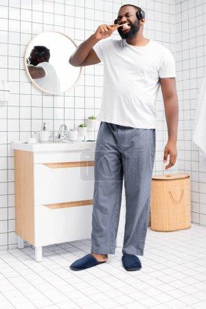 Photo pour Toute la longueur de l'homme afro-américain avec casque brossant les dents - image libre de droit