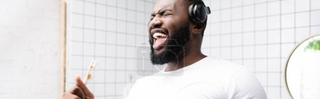 Photo for Panoramic shot of afro-american man with headphones singing in toothbrush - Royalty Free Image