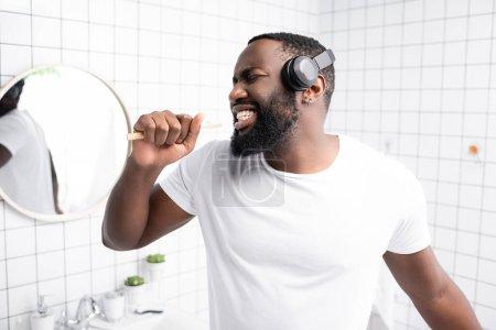 Photo pour Homme afro-américain avec écouteurs chantant dans la brosse à dents - image libre de droit