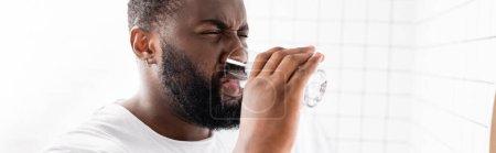 Photo pour Plan panoramique de l'homme afro-américain grimaçant et buvant de l'eau - image libre de droit