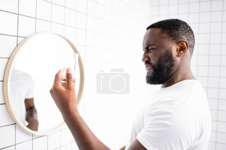 Photo pour Homme afro-américain grimaçant de mauvais goût de l'eau et tenant le verre dans la main - image libre de droit