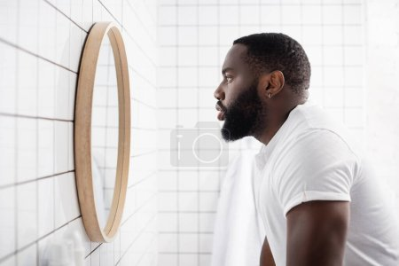 Photo pour Vue latérale d'un homme afro-américain sérieux regardant dans un miroir - image libre de droit