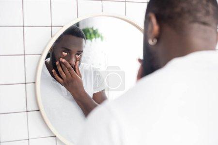 Photo pour Fatigué afro-américain homme tirant les paupières inférieures avec les doigts - image libre de droit