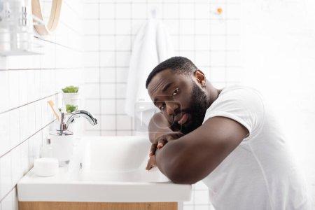 Photo pour Afro-américain homme appuyé sur évier et regardant la caméra - image libre de droit