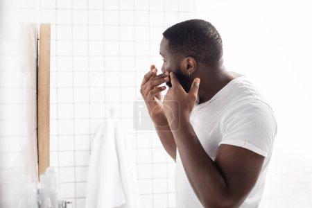 Photo pour Afro-américain homme essayer presser bouton dans salle de bain - image libre de droit