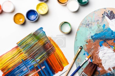 Photo for Top view of gouache paints, paintbrushes and abstract colorful brushstrokes on paper on white background - Royalty Free Image