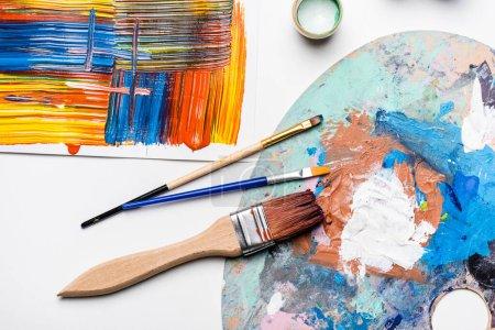 Ansicht von Gouachefarben, Pinseln und abstrakten, bunten Pinselstrichen auf Papier auf weißem Hintergrund