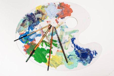 Ansicht der Palette von oben mit Farben und Pinseln isoliert auf Weiß