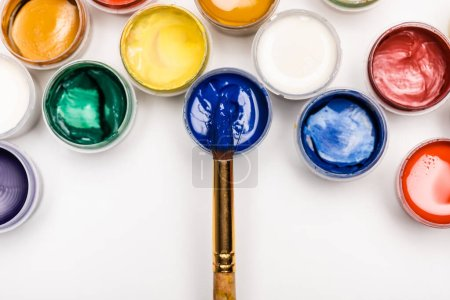 Photo for Top view of colorful Gouache paints and paintbrush on white background - Royalty Free Image