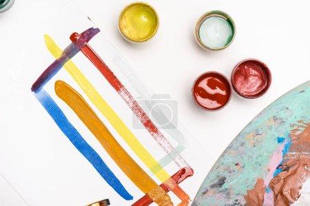 Ansicht der Palette mit Gouachefarben und Pinsel in Papiernähe mit Pinselstrichen auf weißem Hintergrund