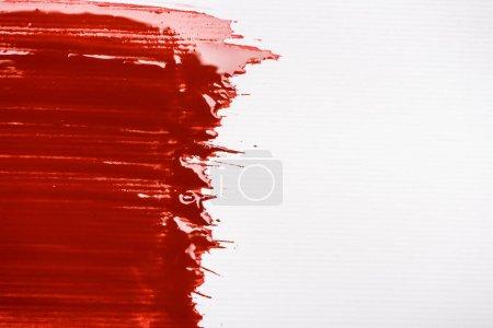vista superior de pincelada colorida de pintura roja sobre fondo blanco