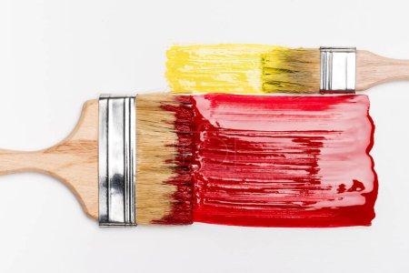 vista superior de pinceles cerca de pinceladas coloridas de pintura roja y amarilla sobre fondo blanco