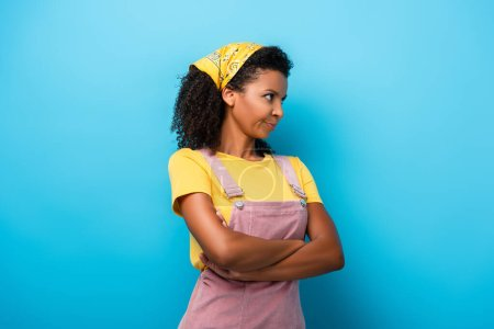 skeptical african american woman standing with crossed arms and looking away on blue