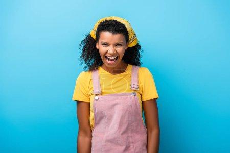 Afrykańska amerykanka z otwartymi ustami śmiejąca się na niebiesko
