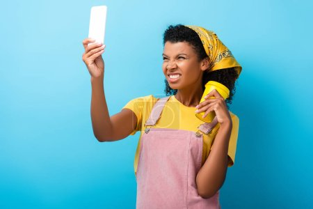 curly african american woman holding reusable mug and showing teeth while taking selfie on blue