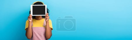 curly african american woman covering face while holding digital tablet with blank screen on blue, banner