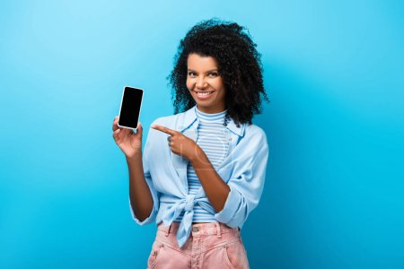 happy african american woman pointing with finger at smartphone with blank screen on blue
