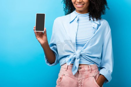 cropped view of happy african american woman holding smartphone with blank screen on blue