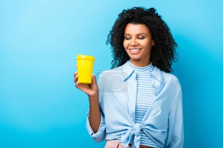 happy african american woman holding empty reusable mug on blue