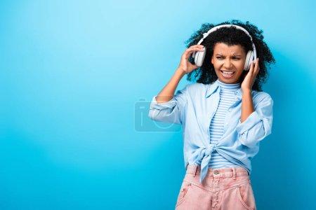 Photo pour Femme afro-américaine mécontente écoutant de la musique dans les écouteurs sur bleu - image libre de droit