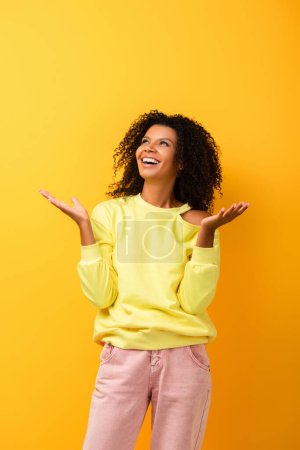 excited african american woman looking up and gesturing on yellow