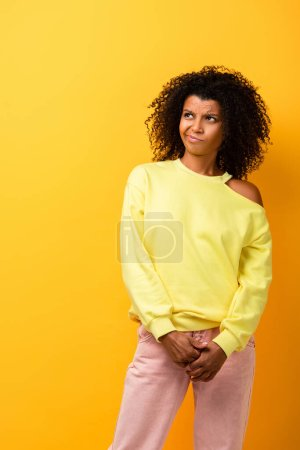 Photo for Displeased african american woman looking away on yellow - Royalty Free Image