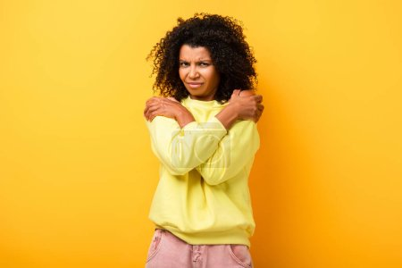 Photo for Displeased african american woman embracing herself on yellow - Royalty Free Image