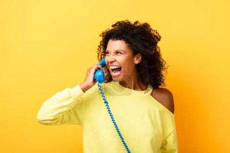curly african american woman laughing while talking on vintage telephone on yellow