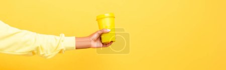 Photo for Cropped view of african american woman holding reusable cup on yellow - Royalty Free Image