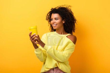 Photo pour Femme américaine africaine gaie tenant éco tasse réutilisable sur jaune - image libre de droit