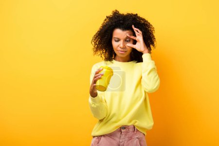 african american woman holding and looking at reusable cup on yellow