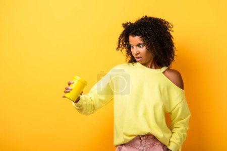 shocked african american woman holding reusable cup on yellow
