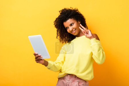 cheerful african american woman holding digital tablet and showing peace sign on yellow