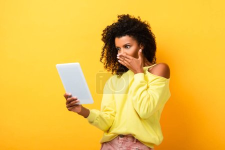 shocked african american woman holding digital tablet on yellow