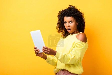 femme afro-américaine choquée tenant tablette numérique et regardant la caméra sur jaune