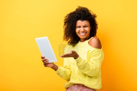 skeptical african american woman pointing with hand at digital tablet on yellow