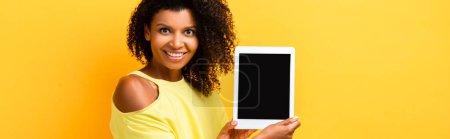 Photo pour Heureuse femme afro-américaine tenant tablette numérique avec écran blanc sur jaune, bannière - image libre de droit