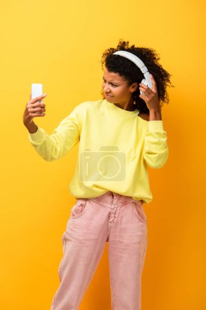 Photo for Dissatisfied african american woman in headphones holding smartphone on yellow - Royalty Free Image