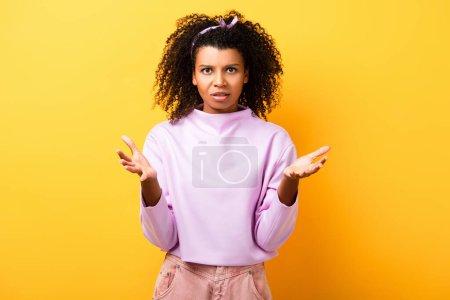 lockige Afroamerikanerin blickt in die Kamera, während sie auf gelb gestikuliert