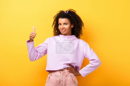 happy african american woman standing with hand on hip and showing thumb up on yellow