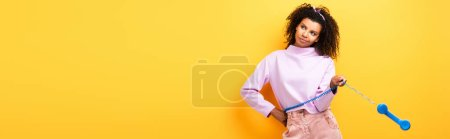 Photo for Displeased african american woman holding blue retro phone on yellow, banner - Royalty Free Image