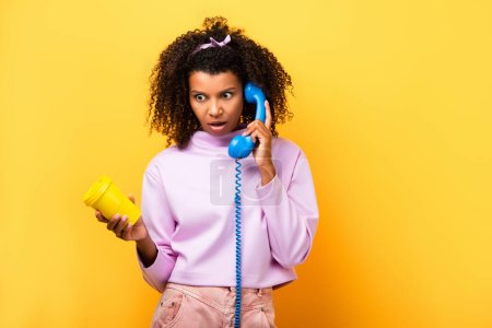 shocked african american woman talking on blue retro telephone and holding eco cup on yellow