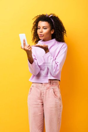 Photo for African american woman holding smartphone and sending air kiss on yellow - Royalty Free Image
