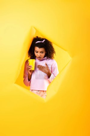 Photo for Surprised african american woman holding disposable cup and looking down through hole in ripped paper on yellow background - Royalty Free Image